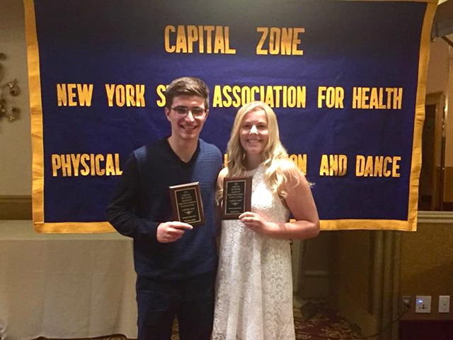 two winners hold small plaques while standing in front of Capital Zone banner