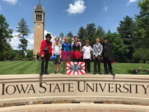 students by Iowa State University sign