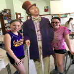 two girls stand next to a cardboard Willy Wonka figure