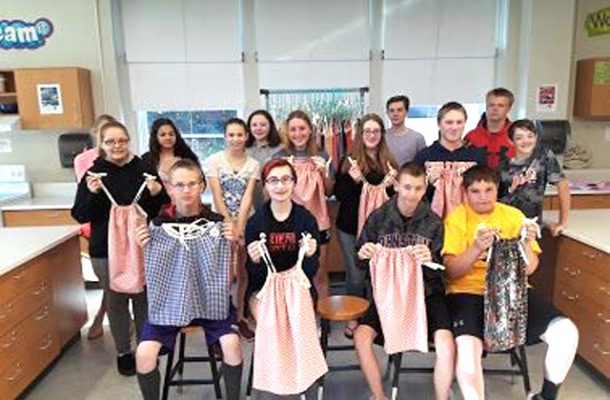 group photo of students holding up dresses