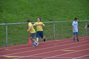 two students transferring baton in relay
