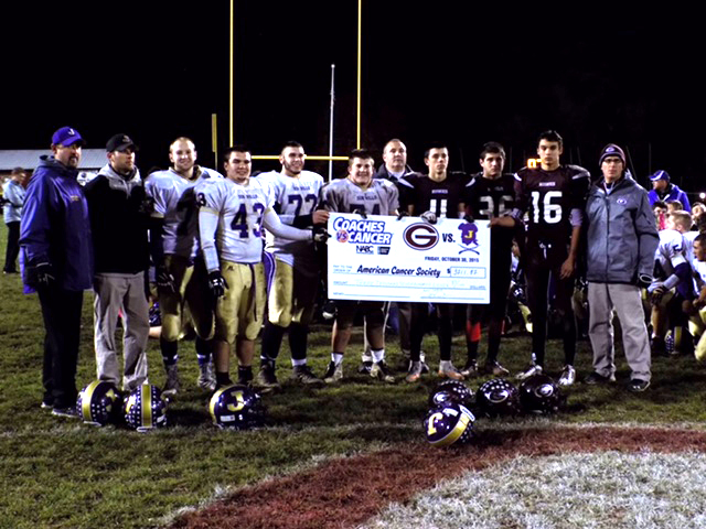 players, coaches, ADs pose with large check