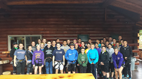 group photo in front of log cabin building