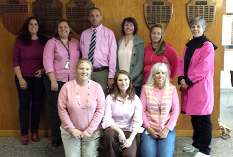 staff members pose dressed in pink