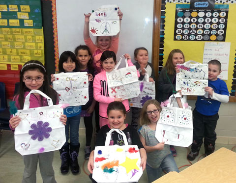 students pose with decorated tote bags
