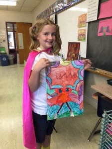 girl in pink cape holds her drawing