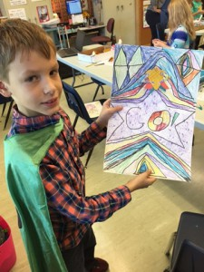 boy in green cape holds his drawing