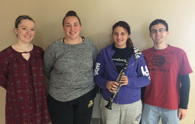 four students pose, one with clarinet