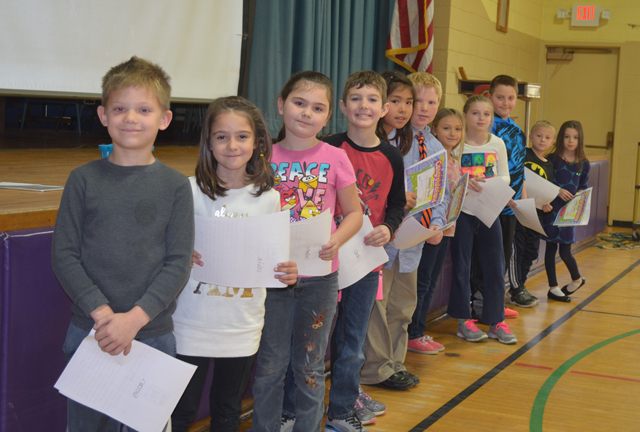 students of the month line up in front of stage