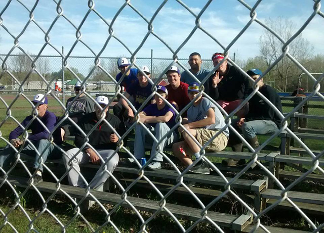 players coaches on bleachers behind chain link fence