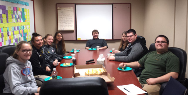 students sit at conference room table with plates