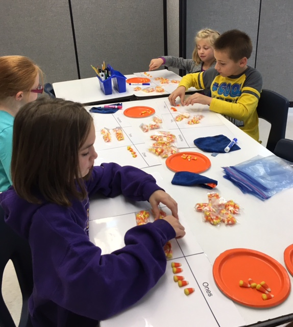 group of students seated around table with plates of candy corn
