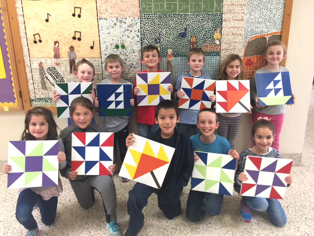 group of students pose with quilt squares they painted