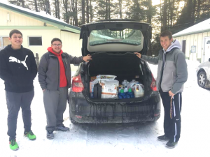 council officers stand next to vehicle with trunk open to show donated items