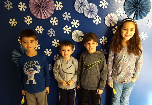 four children pose against wall