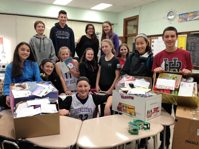 students pose in group with boxed items on desks