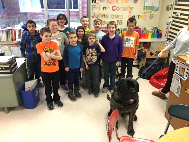 group shot of students with dog sitting in front of them