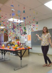 Ms. Kelly in classroom under mobiles