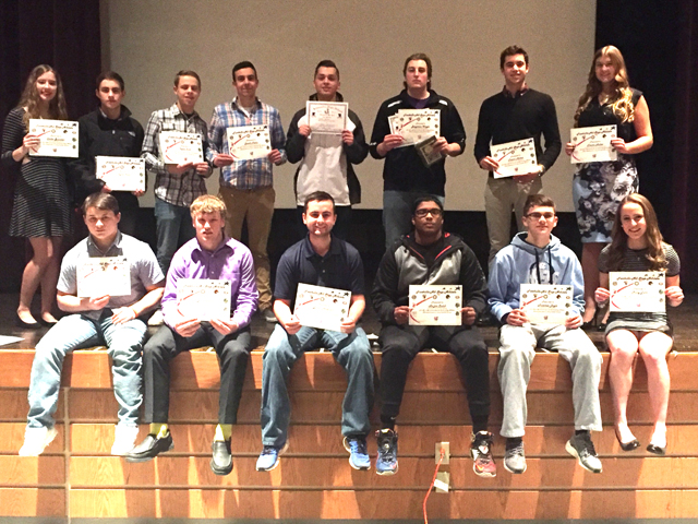 group photo of student athletes sitting and standing on lecture hall stage holding certificates