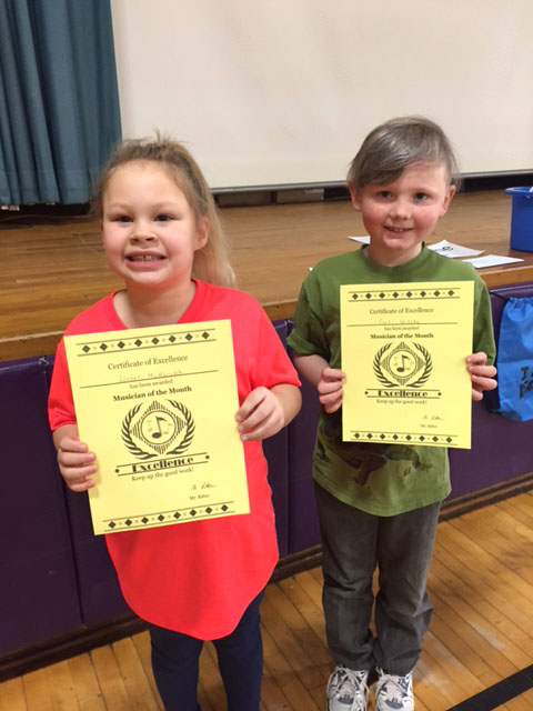 two students holding certificates