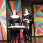 two girls dressed as nuns stand on stage