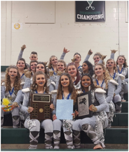 group shot of varsity winter guard holding championship plaques and raising hands int he air