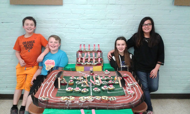 winning team poses with cupcake display replica of football field & track