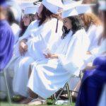 graduates sitting on field