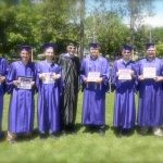 male students pose for group photo with their diplomas displayed
