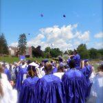 graduates look at balloons floating away
