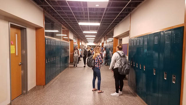 students walk by lockers in hallway