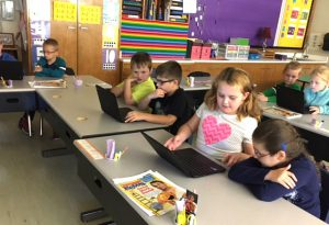 students sit together at tables with Chromebooks in front of them