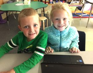 boy and girl smile at camera with a Chromebook in front of them