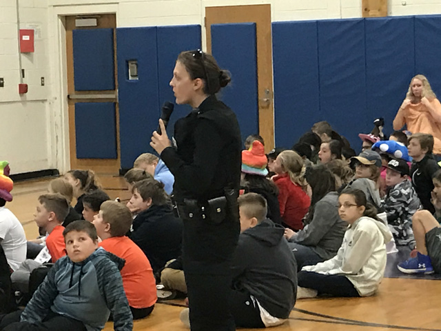 police officer uses microphone to address students