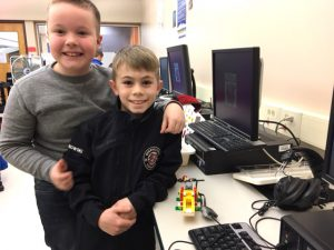 two boys stand by computer and smile