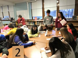 students gather around table with a number 2 on it