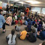 kids sit on library floor