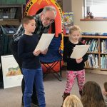 Gary VanRiper stands by boy & girl reading from papers