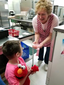 boy iin pink shirt with muppet visting cafeteria worker