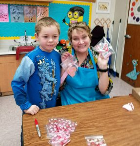 boy in blue shirt with art teacher Mrs. Fisk