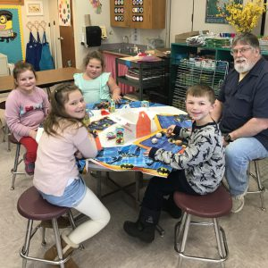 four students sit at round table with Mr. Forgette