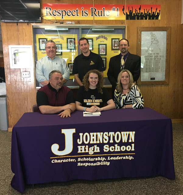 Emily at table to sign letter, surrounded by her parents, Johnstown AD Mr. Robare, and St. Rose swim coaches