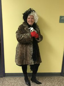 Principal Cory Cotter dressed as Cruella De Vil holds a stuffed dog