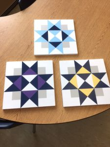 3 quilt squares displayed on table