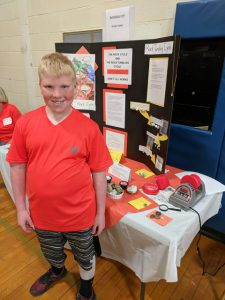 boy standing next to table displaying a project