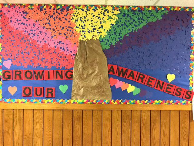 "colorful tree created from paper and attached to the wall with words ""showing awareness"""