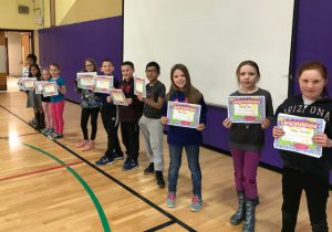Students of the Month line up with certificates