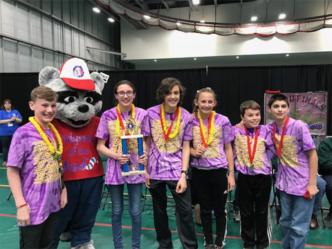 students pose at end of competition with trophy and odyssey mascot