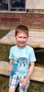 little boy sitting at picnic table