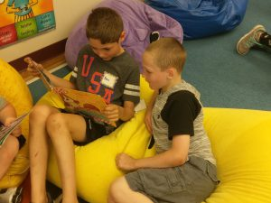 two boys reading on bean bags